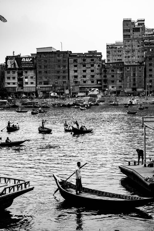 Grayscale Photo of People Riding on Boat on River