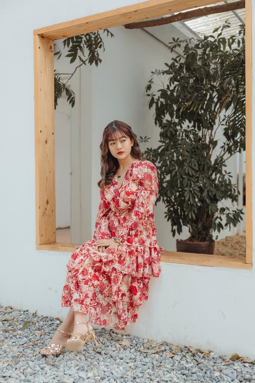 Woman in Red Floral Dress Standing Near Green Plant