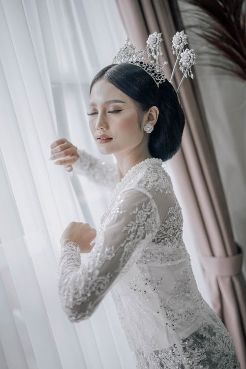 Woman Wearing a White Lace Long Sleeve Dress Holding a Curtain