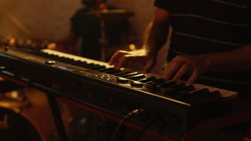 Person Playing Brown and Black Electric Keyboard
