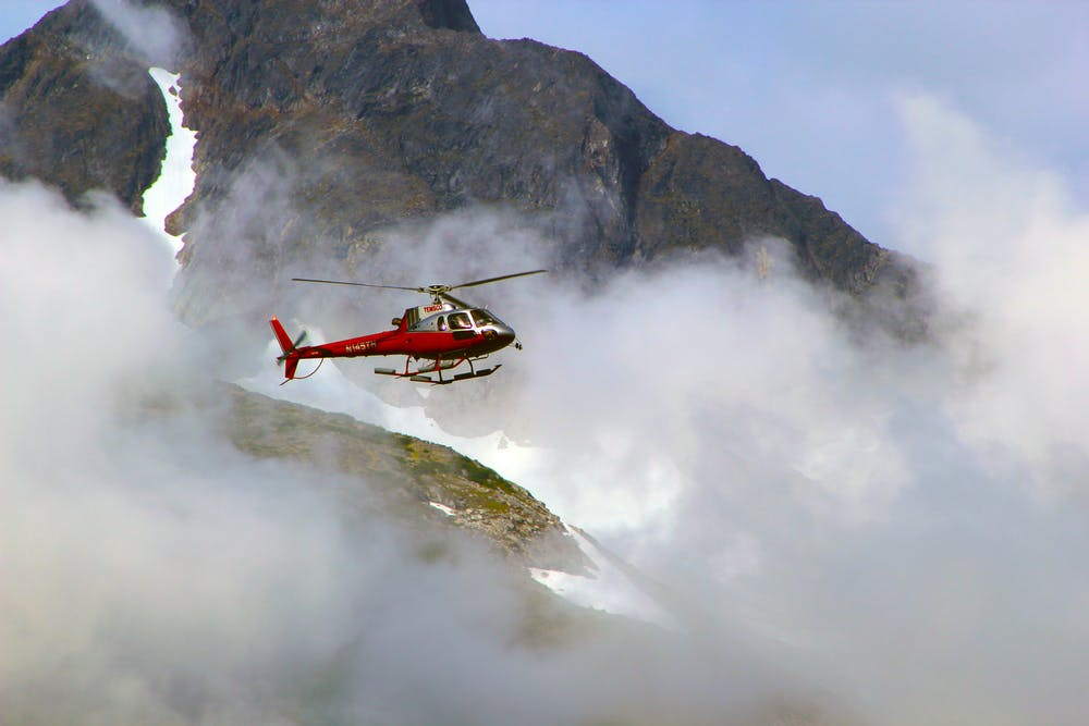Red helicopter on top of foggy mountain. | Photo: Pexels
