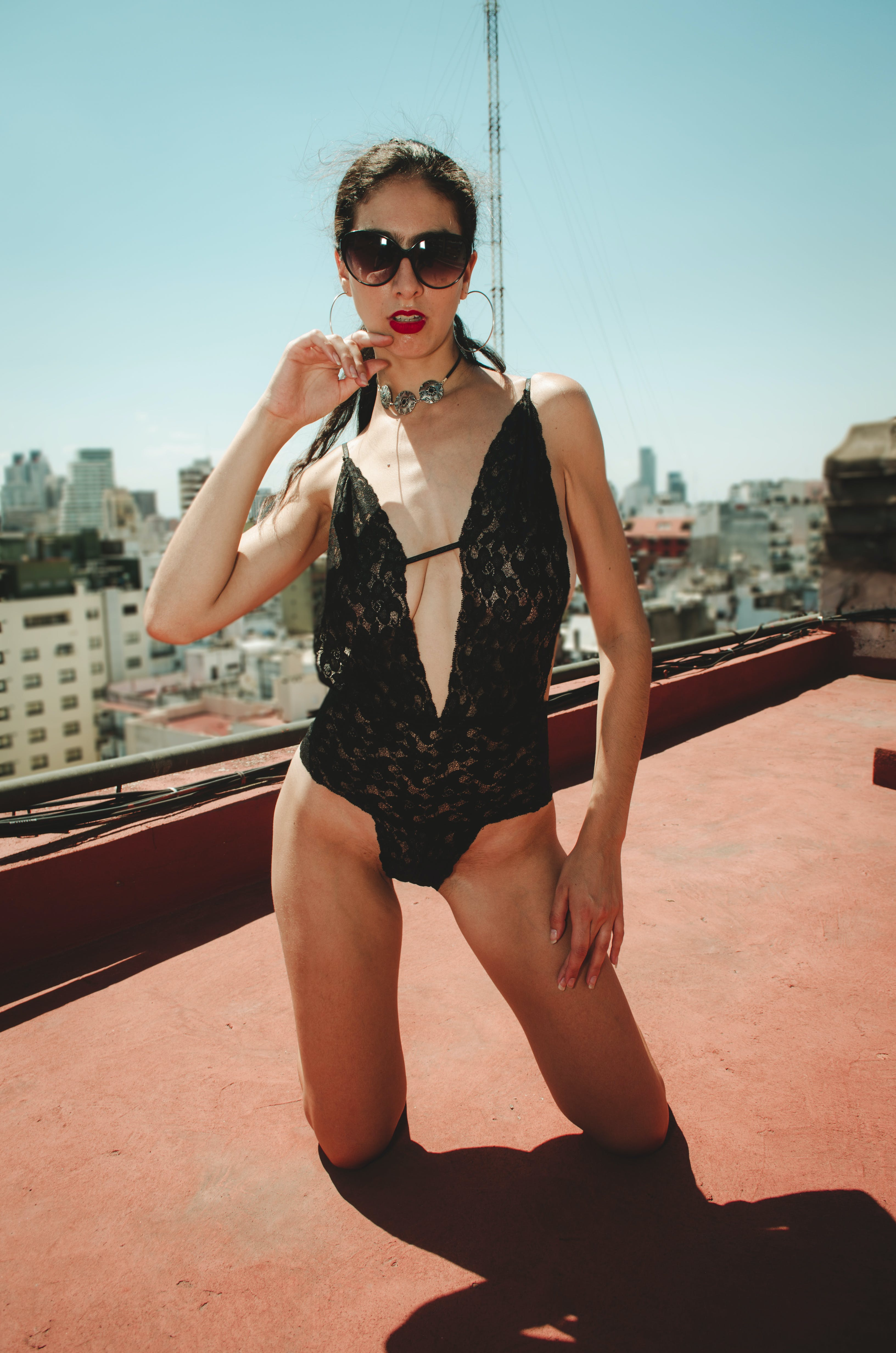 Kneeling Woman Wearing Black Spaghetti-strap One Piece Swimsuit