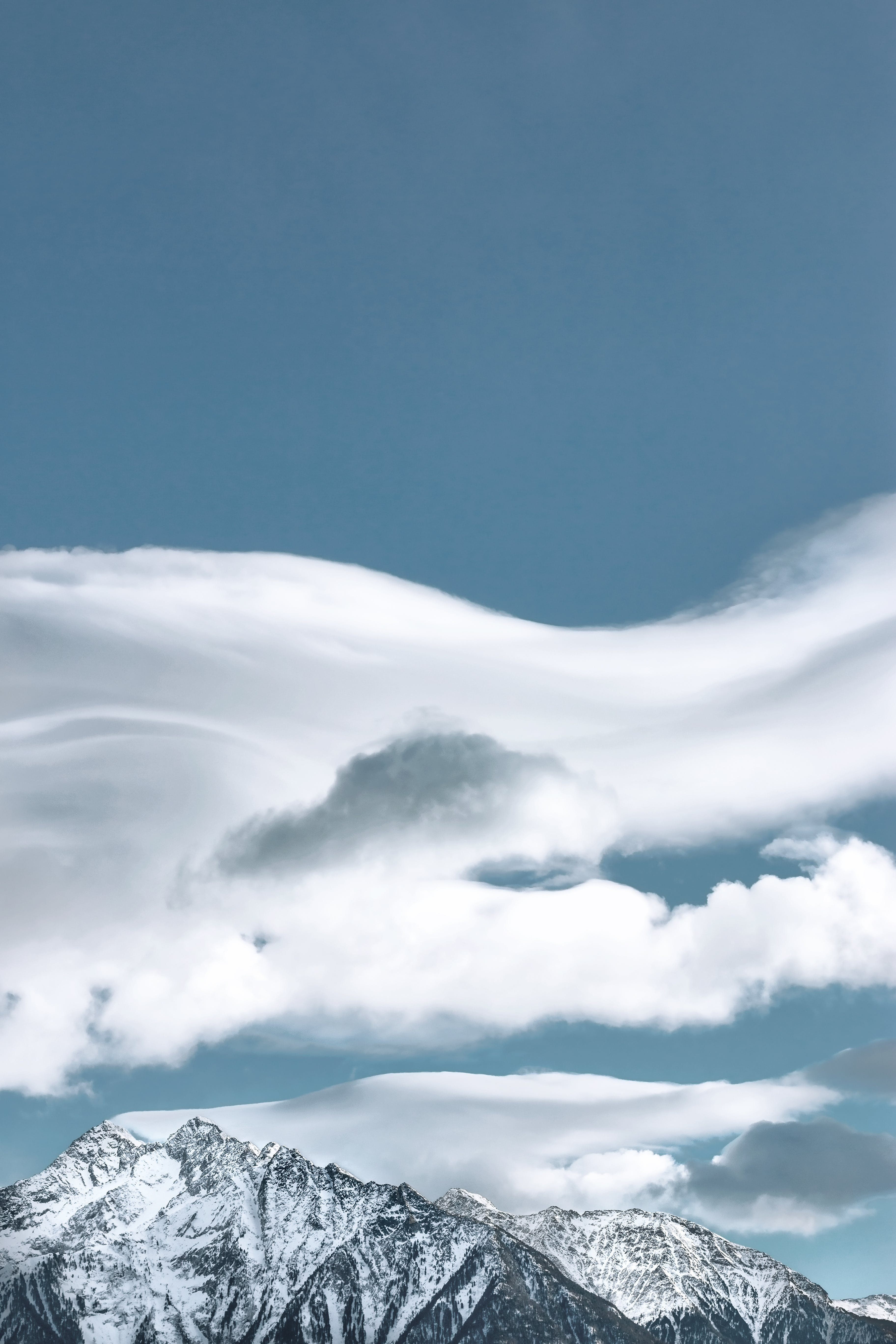 Cloud Formation Above Snow-capped Mountain