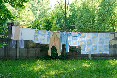 Clothes and Sheets Hanging on a Clothespin During Daytime