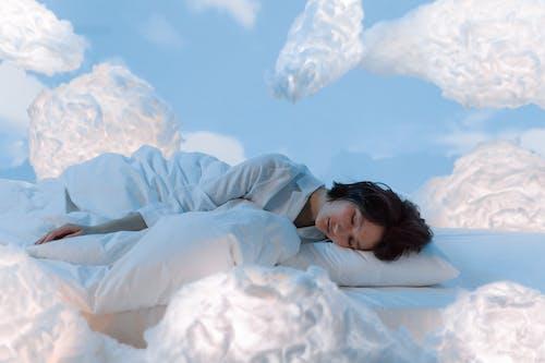 Photo of a Woman Sleeping Near Fluffy Clouds