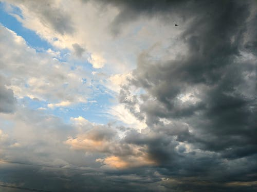 Gray cumulus thick clouds floating high in air on blue sky in overcast weather in nature on gloomy summer day