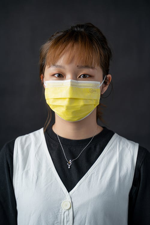 Portrait of a Woman Wearing a Yellow Face Mask