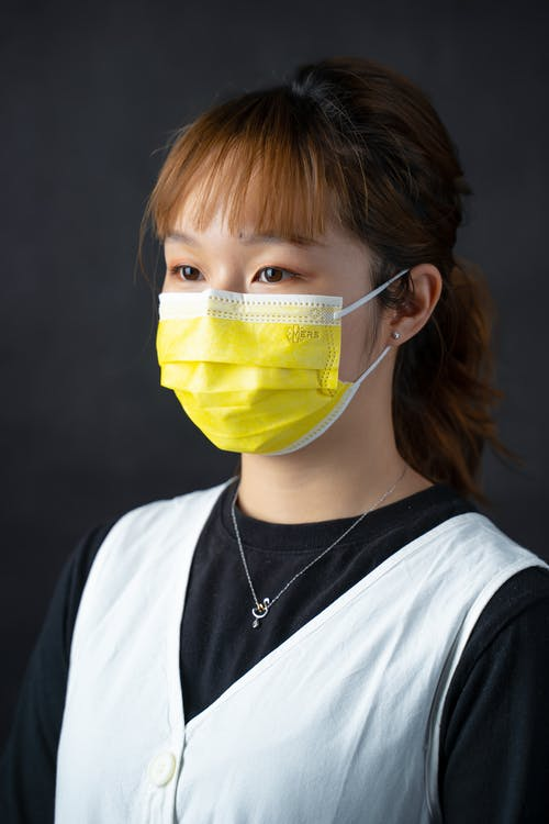 Close-Up Photo of a Woman Wearing a Yellow Face Mask