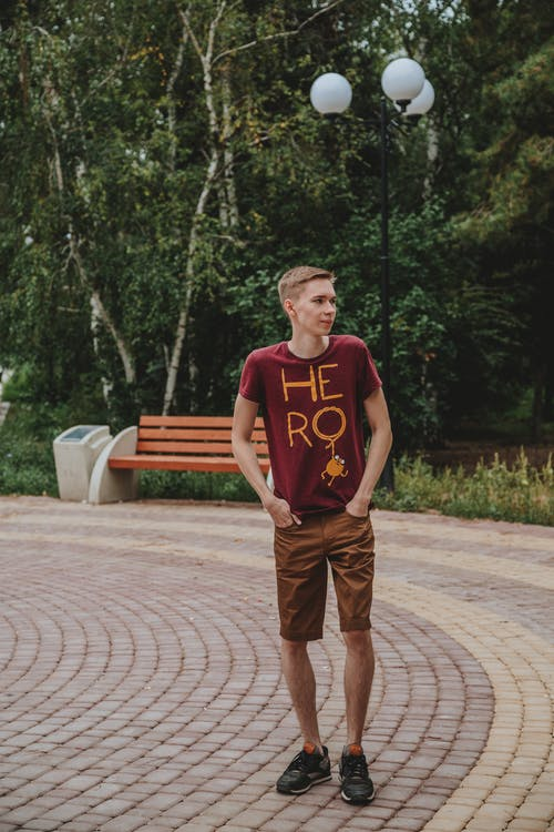Man in Red Crew Neck T-shirt and Brown Pants Standing on Brown Wooden Bench during