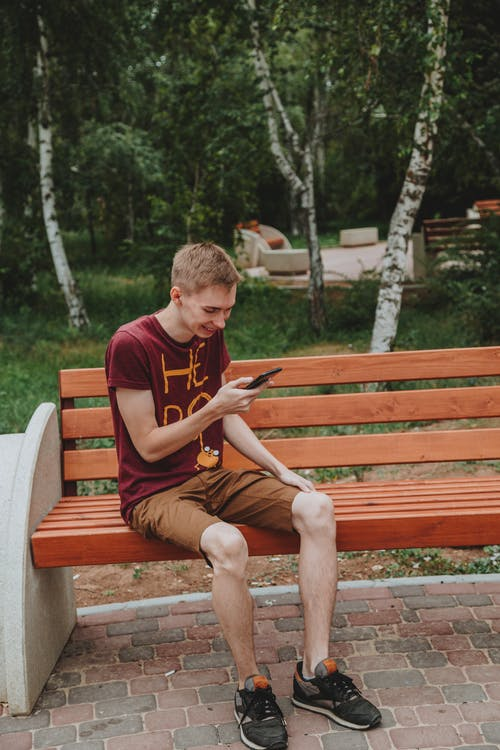 Man in Red Crew Neck T-shirt Sitting on Brown Wooden Bench