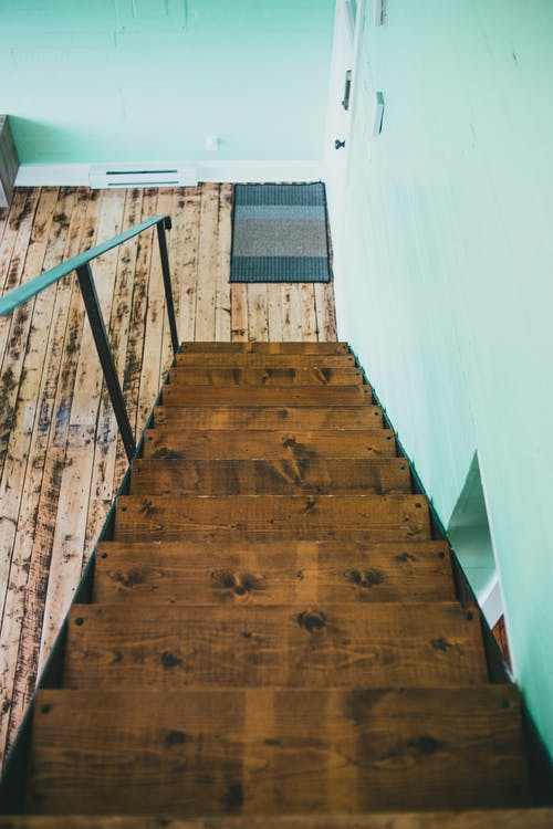 Photo of a Brown Wooden Staircase with a Metal Handrail