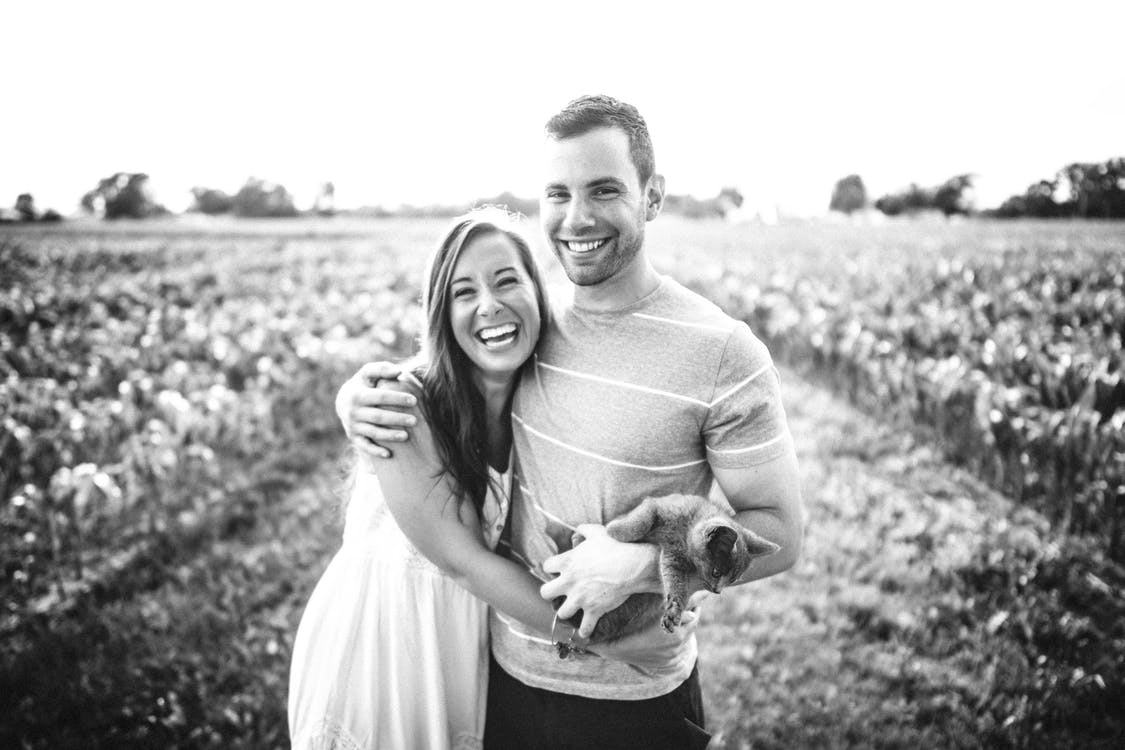 Grayscale Photography of Man and Woman Hugging Each Other Beside Plant Fields