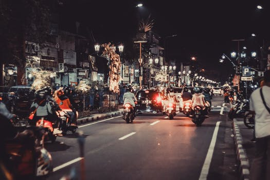People Riding Motorcycles On Road During Night Time