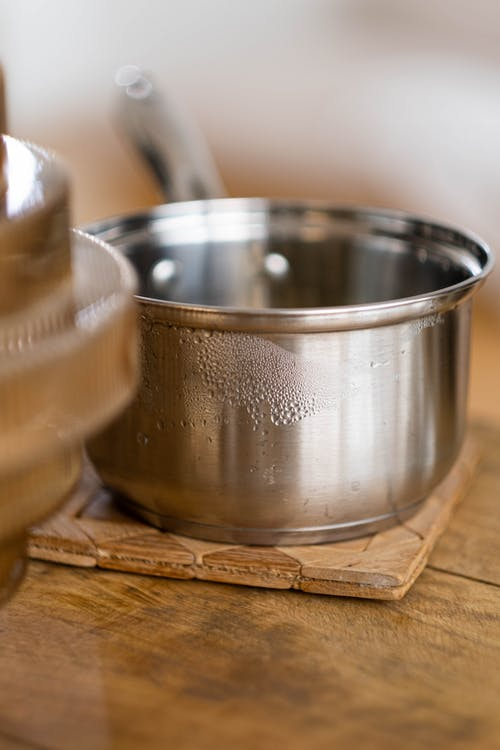 Stainless Steel Pot on Brown Wooden Board