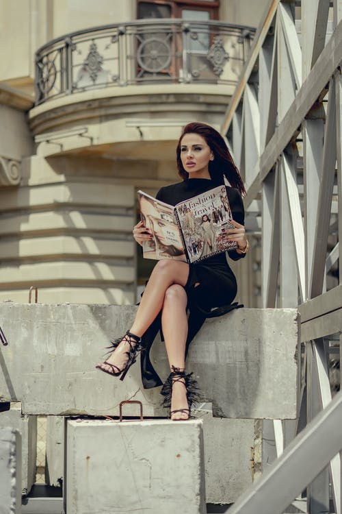Full body of charming female in elegant dress reading magazine and looking away while sitting on cement border near residential building on street