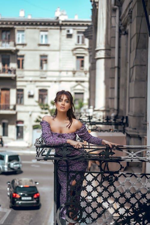 Charming woman in dress on balcony