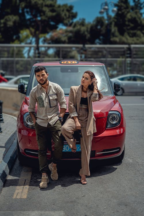 Full body of serious couple in trendy outfits looking at camera while leaning on modern automobile parked on sunny street
