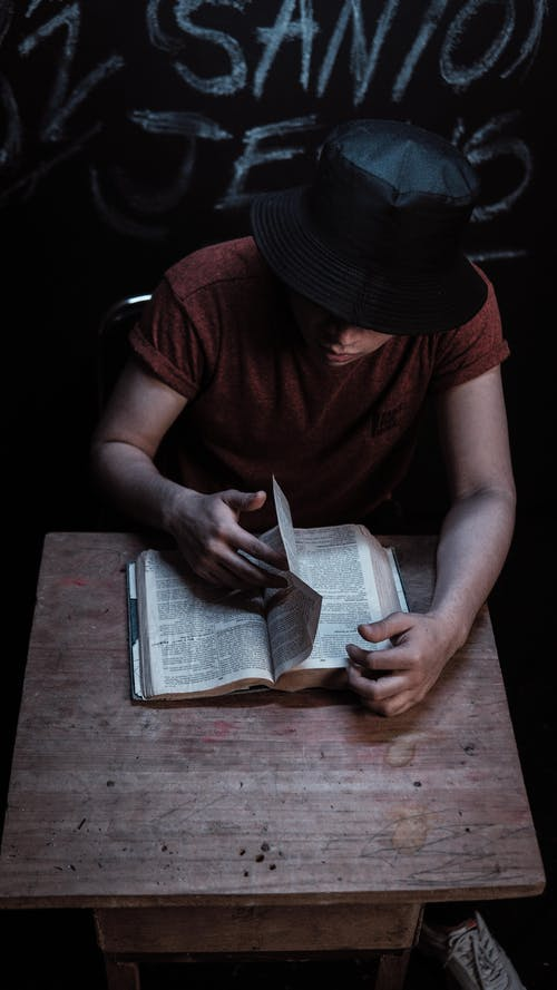 A Person in Red Shirt and Black Hat Reading a Book