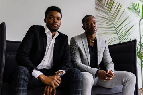 Men Wearing Suits Sitting on a Couch