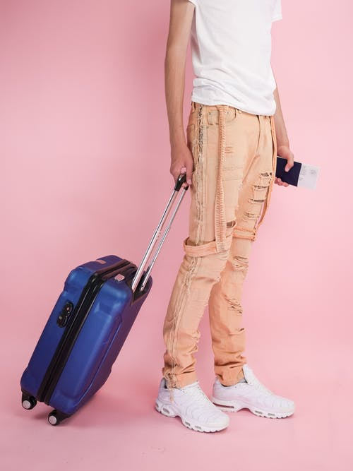 Man in White Tank Top and Brown Pants Holding Red Luggage Bag
