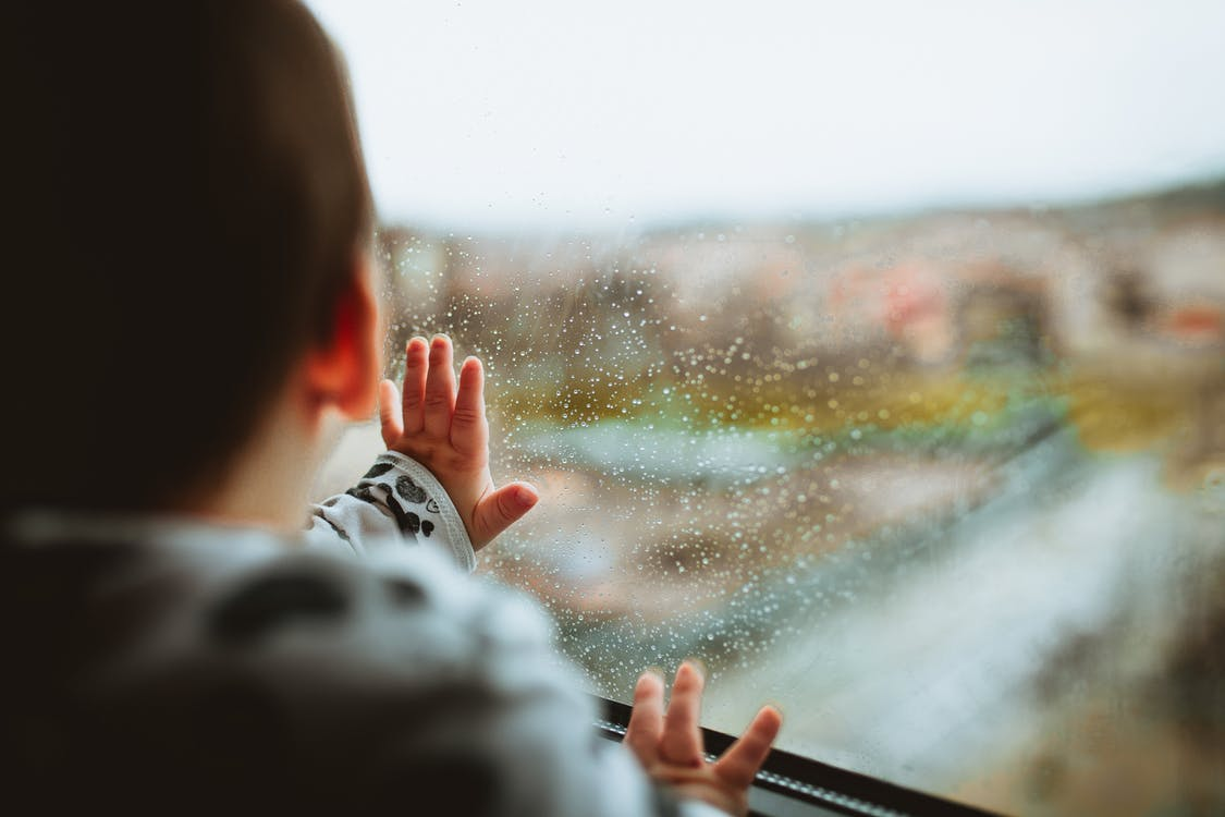 Selective Focus Photography of a Baby Looking Through The Window