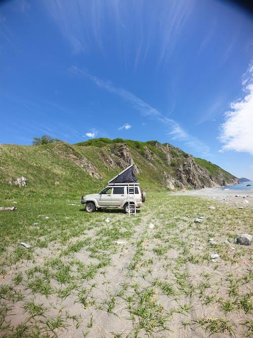 White Car on White Sand Near Green Mountain Under Blue Sky