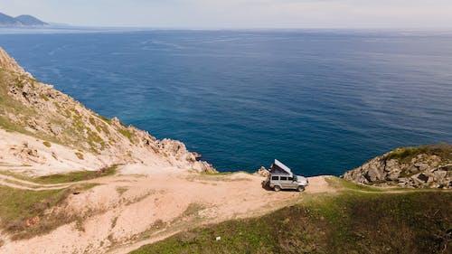 White Car on Brown Rocky Mountain Beside Blue Sea