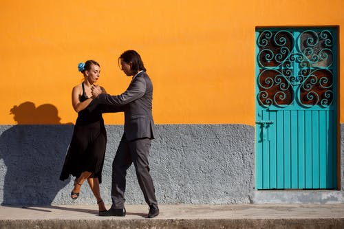 Man and Woman Kissing Near Blue and Orange Wall