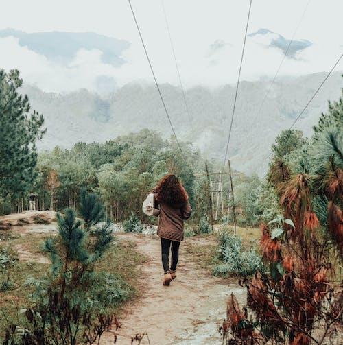 Woman in Brown Jacket Walking on Dirt Pathway Between Green Plants