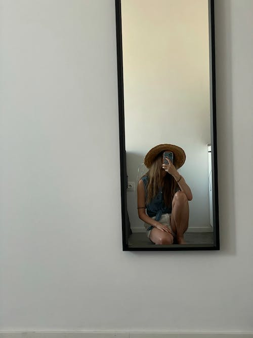 Woman in Blue Tank Top and Brown Fedora Hat Sitting on White Wall