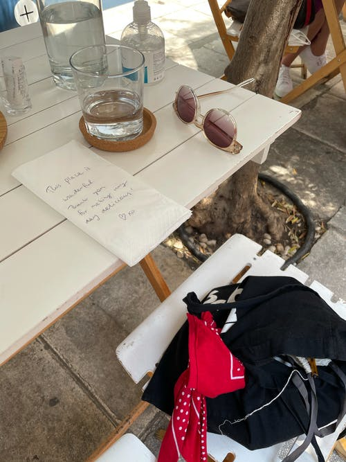Brown Sunglasses Beside Clear Drinking Glass on Table