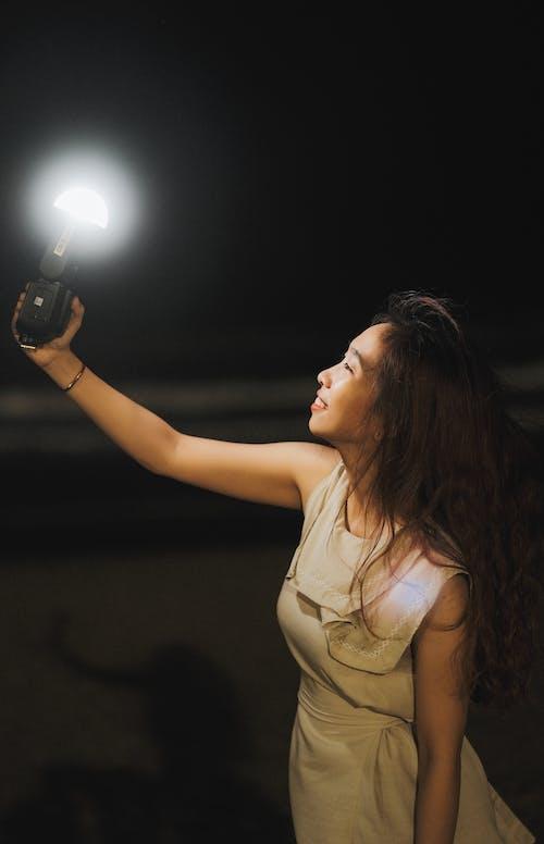 Woman in Brown Tank Top Holding Black Dslr Camera