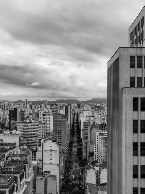 Grayscale Photo of City Buildings Under Cloudy Sky