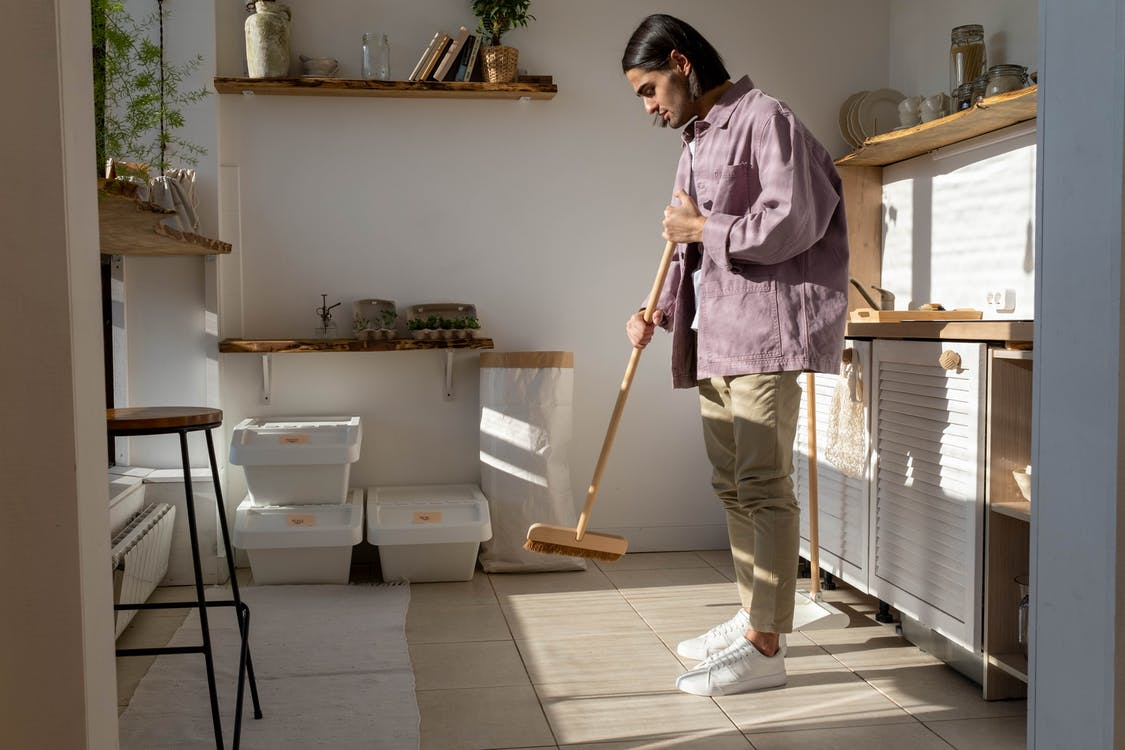 A Man Sweeping the Kitchen Floor