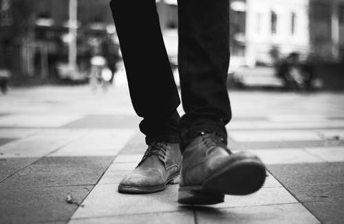 Grayscale Photo of a Person Walking in Formal Shoes