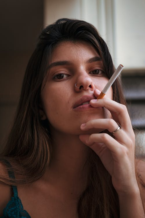 Woman in Gray Sweater Smoking Cigarette
