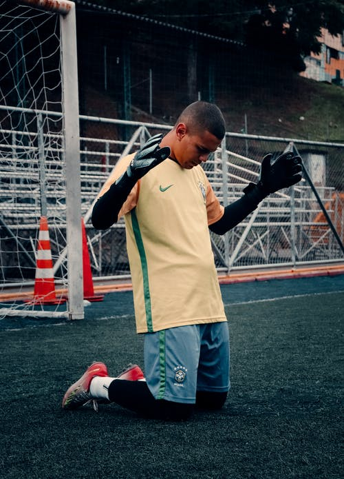 A Football Goalie Kneeling on the Field