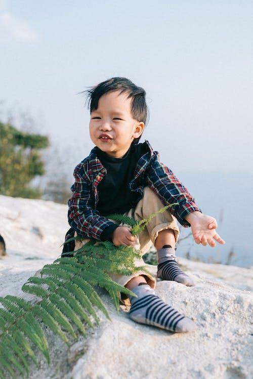 A Child Holding a Fern Leaf