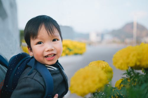 Close-Up Photo of a Boy Carrying a Backpack Near Yellow Flowers