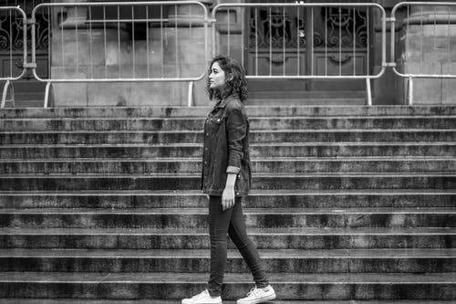 Grayscale Photo of a Woman Walking Near Concrete Steps