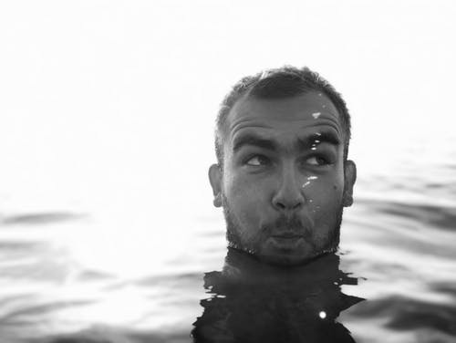 Grayscale Photo of a Man's Head Above Water