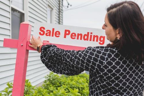 A Realtor Putting Up a Sale Pending Signboard
