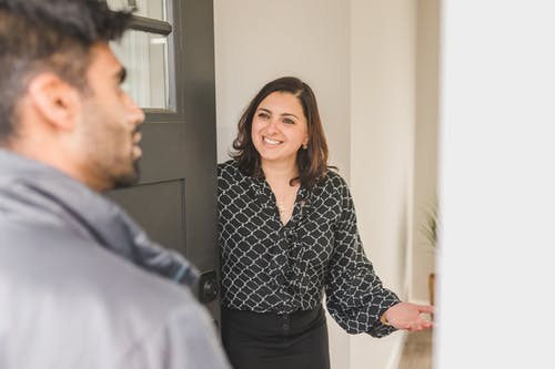 A Realtor Welcoming a Client into the House