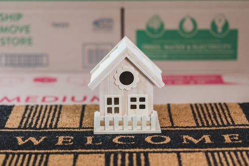 White Wooden House Miniature on Brown and Black Textile