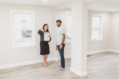 Woman Showing the Inside of House to a Man