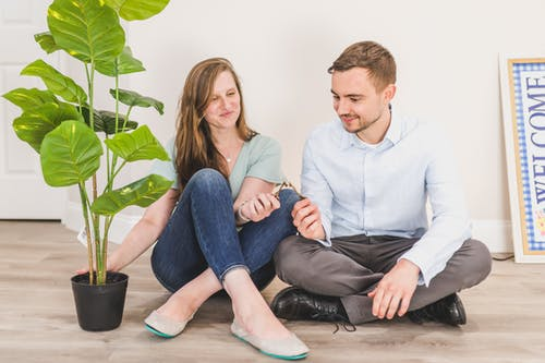 Man and Woman Sitting on the Floor while Holding Keys
