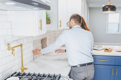 Real Estate Agents Checking the Tiles in the Kitchen