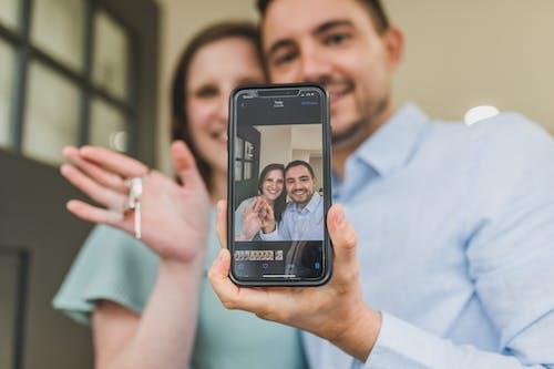 adam, akıllı telefon, çift içeren Ücretsiz stok fotoğraf