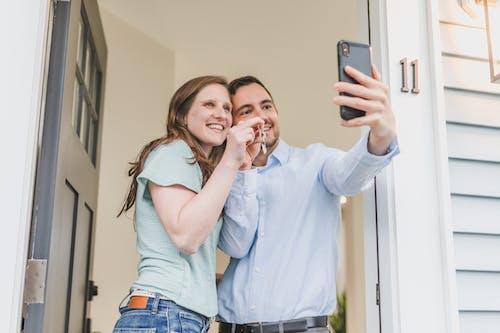 Couple Having Group Selfie while Holding Key