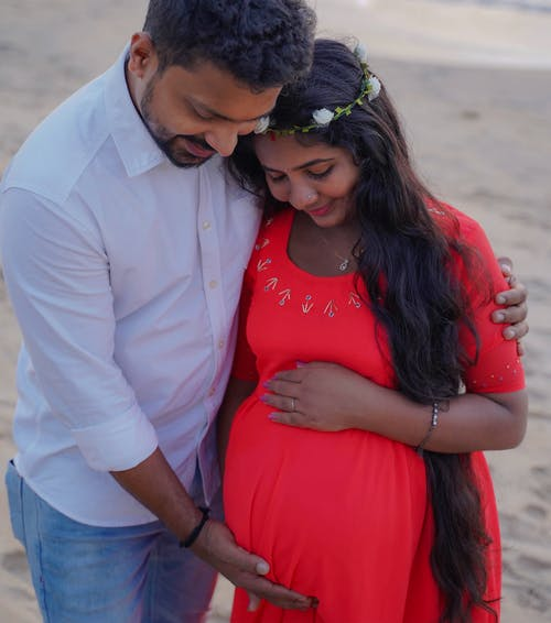 Pregnant Woman Wearing Red Dress with a Man